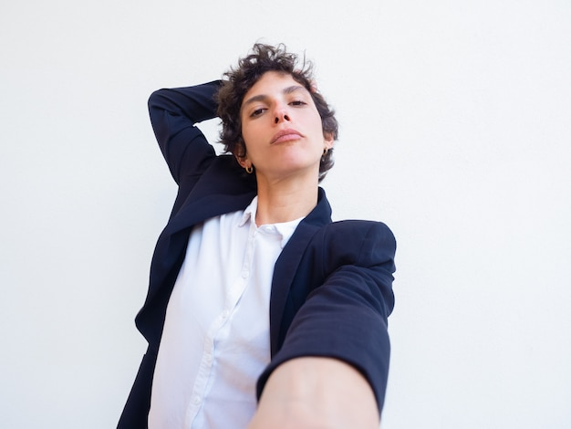 Confident androgynous young woman holding cell phone Free Photo