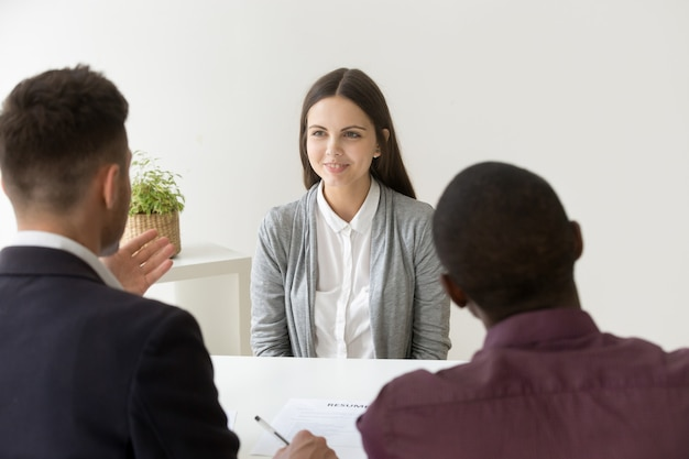 Confident applicant smiling at job interview with diverse hr managers Free Photo