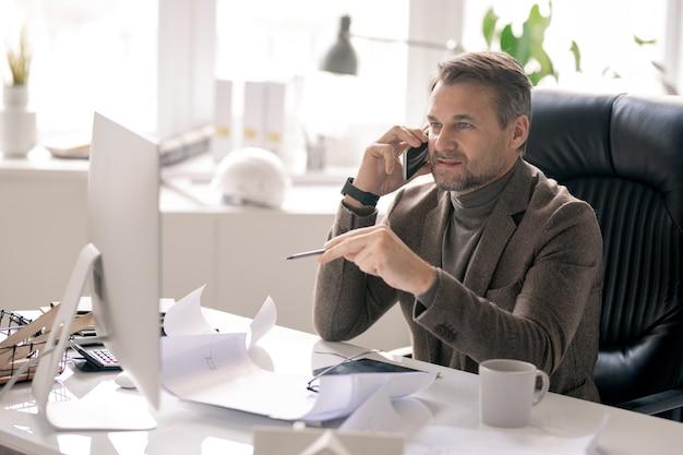 Уверенный архитектор в строгой одежде разговаривает по телефону, указывая на экран компьютера на рабочем месте Premium Фотографии