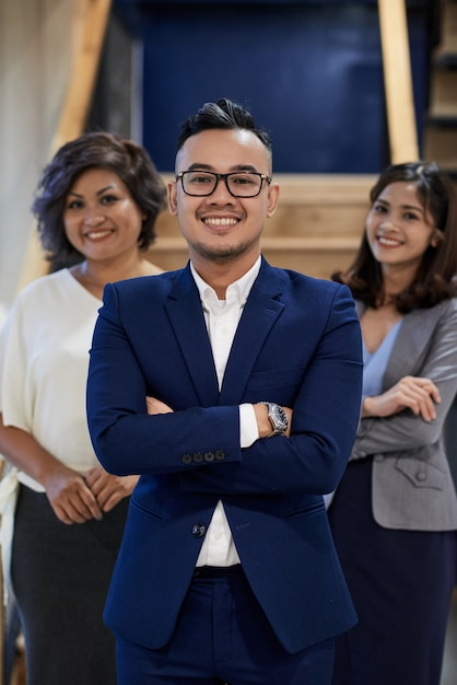 Confident asian businessman posing with crossed arms, and two female colleagues standing behind Free Photo