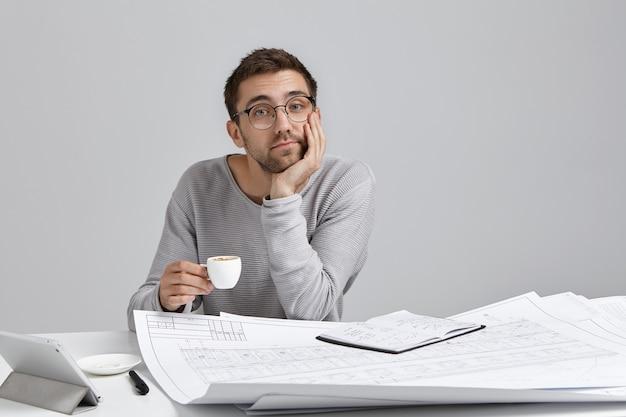 Fiducioso uomo attraente, tiene la tazza di cappuccino, si siede al tavolo circondato da schemi e schizzi Foto Gratuite