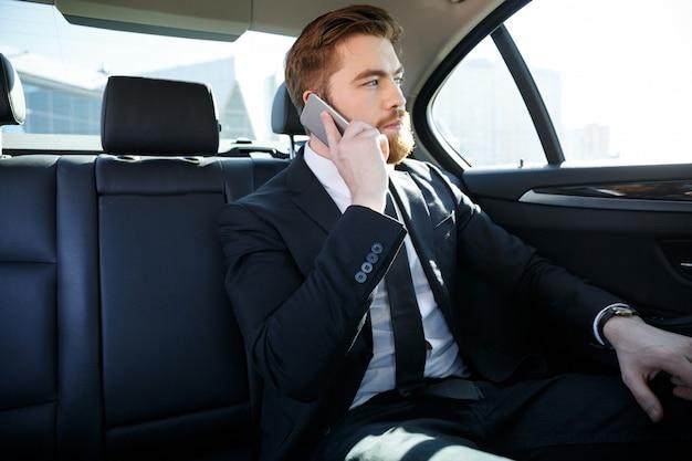 携帯電話で話している自信を持ってのひげを生やした実業家 無料写真