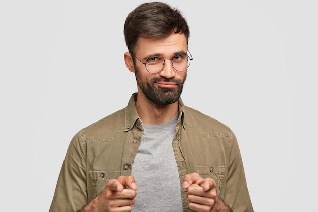 Уверенно бородатый мужчина показывает обоими указательными пальцами, что-то выбирает, имеет темную щетину, стоит особняком у белой стены. привлекательный уверенный в себе мужчина-ушавен высказывает свой выбор Бесплатные Фотографии