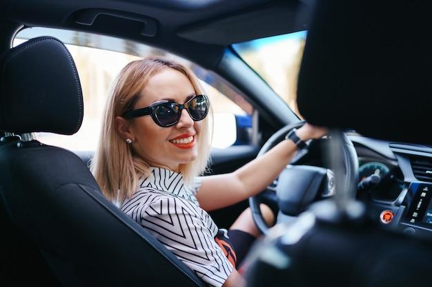 Donna sicura e bella in occhiali da sole. vista posteriore della giovane femmina attraente in abbigliamento casual alla guida di un'auto Foto Gratuite