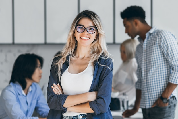 Confident blonde female manager posing with smile after conference with other employees. asian programmer talking with african freelancer while fair-haired secretary laughing. Free Photo