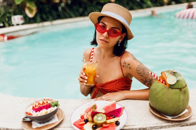 Уверенно брюнетка загорелая женщина в красных кошачьих глаз солнцезащитные очки отдыха в бассейне с тарелкой экзотических фруктов во время тропического отпуска. стильная татуировка. Бесплатные Фотографии
