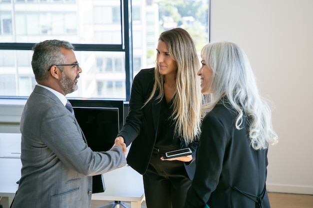 Confident business partners meeting in office, standing and shaking hands, talking, discussing collaboration. medium shot. communication or partnership concept Free Photo