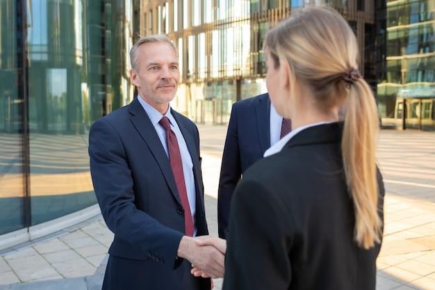 Fiduciosi partner commerciali in piedi vicino a edifici per uffici, si stringono la mano, si incontrano e parlano in città. discussione del contratto e concetto di partenariato Foto Gratuite