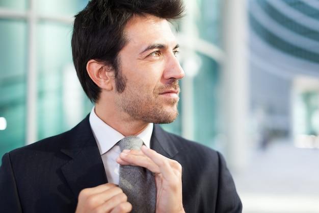 Confident businessman adjusting his necktie Premium Photo