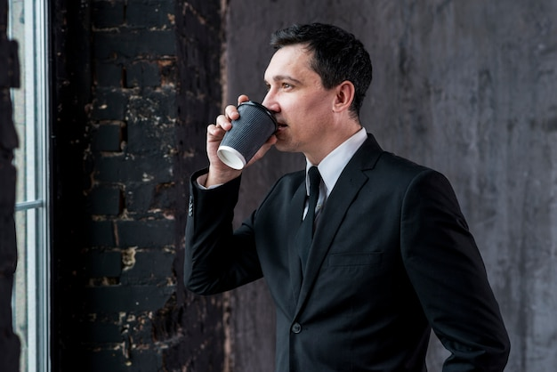 Confident  businessman drinking coffee from paper cup Free Photo