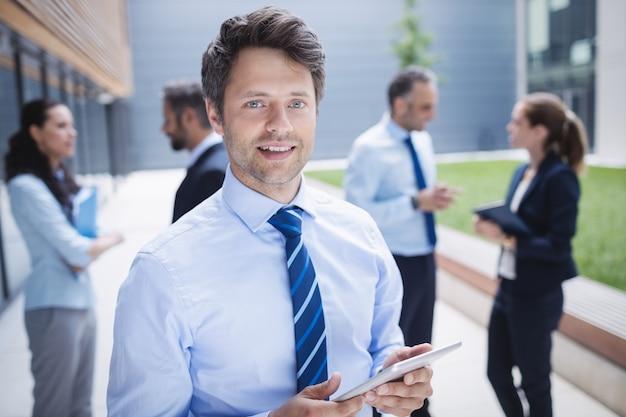 Uomo d'affari sicuro che tiene compressa digitale fuori dell'edificio per uffici Foto Gratuite