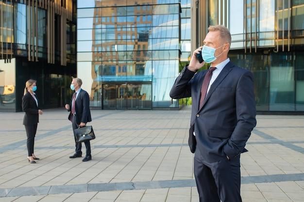 Fiducioso imprenditore indossando maschera e tuta da ufficio parlando al cellulare all'aperto. imprenditori e città edificio facciata in vetro in background. copia spazio. concetto di affari ed epidemia Foto Gratuite
