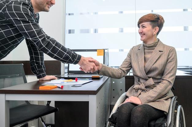 車椅子の握手で自信を持って女性実業家 無料写真