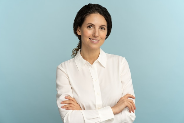 Confident businesswoman, smiling, looking at camera, crossed arms posing isolated on blue background Premium Photo
