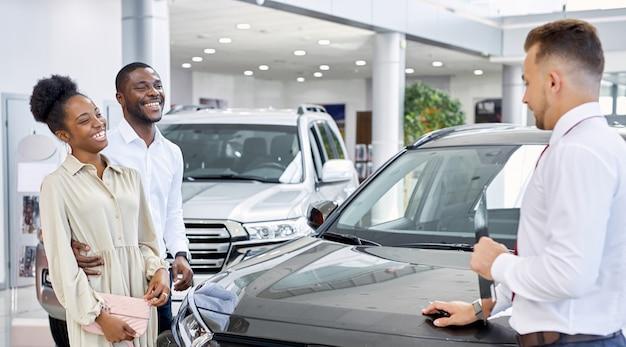 自動車販売店で車を販売する自信を持って白人男性の販売員 Premium写真