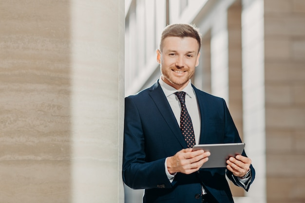 Confident cheerful male lawyer reads business news, has gentle smile Premium Photo