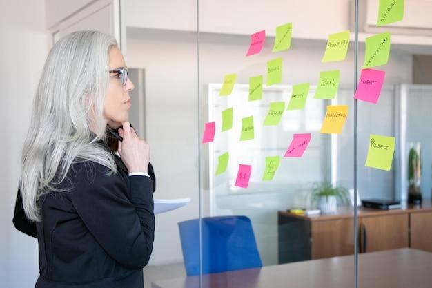 Fiduciosa imprenditrice concentrata guardando gli adesivi sulla parete di vetro. lavoratore femminile dai capelli grigi concentrato che pensa alle note per la strategia di progetto. marketing, affari e concetto di gestione Foto Gratuite