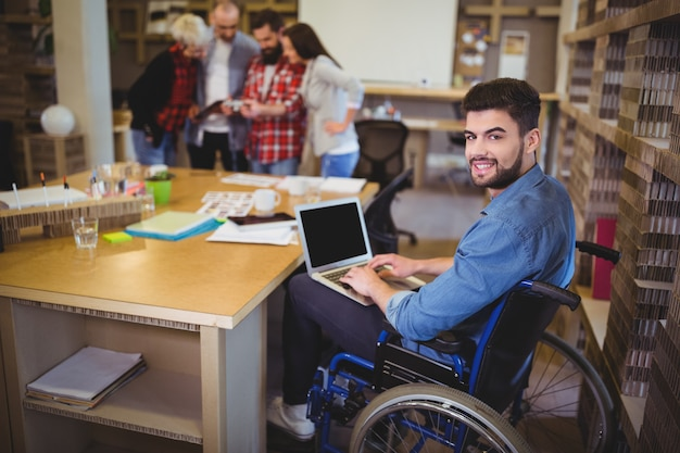 Confident disabled businessman using laptop at desk Premium Photo