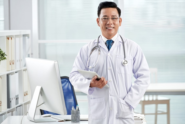 Confident doctor looking at camera holding the tablet pc Free Photo