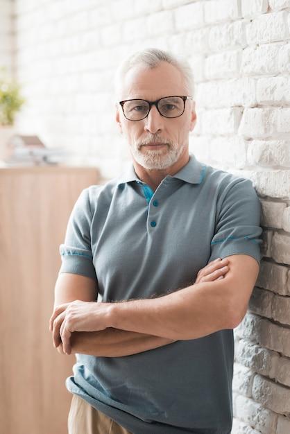 Confident elderly man in glasses with crossed arms. Premium Photo