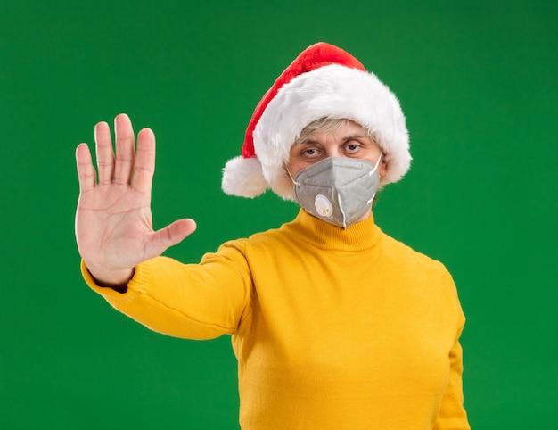 Fiduciosa donna anziana con santa hat indossando maschera medica gesticolando stop isolato su sfondo verde con copia spazio Foto Gratuite