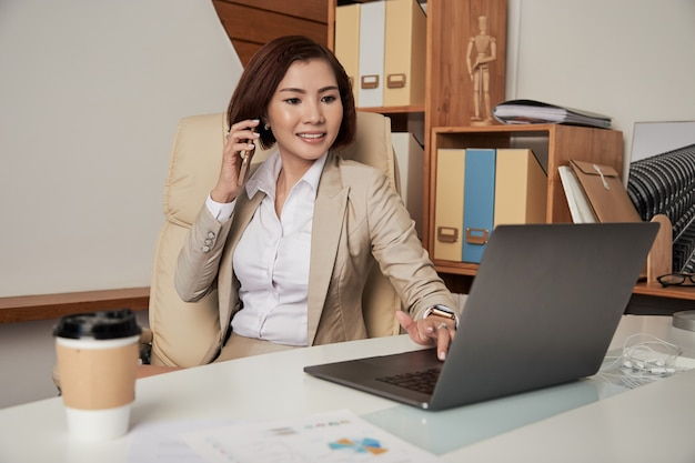 Confident ethnic businesswoman speaking on phone in office Free Photo