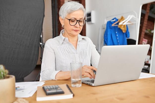 ラップトップで高速ワイヤレスインターネット接続を使用して、クライアントやビジネスパートナーに手紙を入力するスタイリッシュな眼鏡をかけている自信のある経験豊富な成熟した実業家。 無料写真
