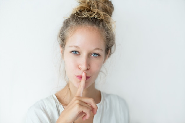 Confident face of young woman with finger on lips Free Photo