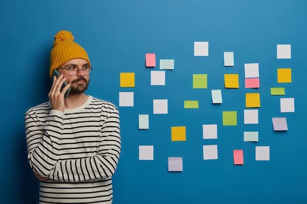 Fiducioso ragazzo alla moda scambia idee creative con un collega o un partner tramite telefono cellulare, distoglie lo sguardo, si erge su sfondo blu con piccole note pulite Foto Gratuite