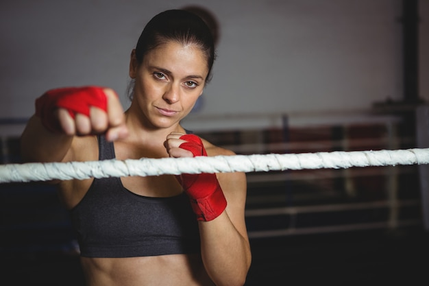 Confident female boxer performing boxing stance Free Photo