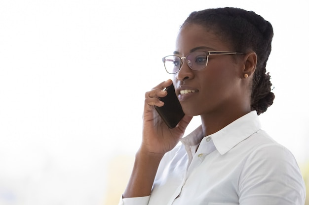 Confident female consultant talking on mobile phone Free Photo