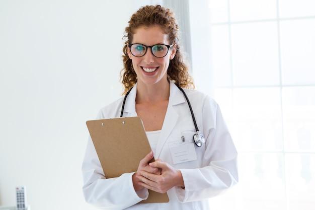 カメラを見ているオフィスで自信ある女性医。 Premium写真