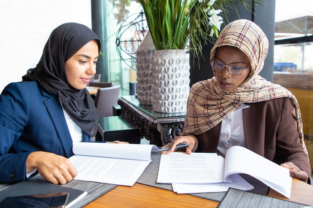 Confident female professionals checking documents Free Photo