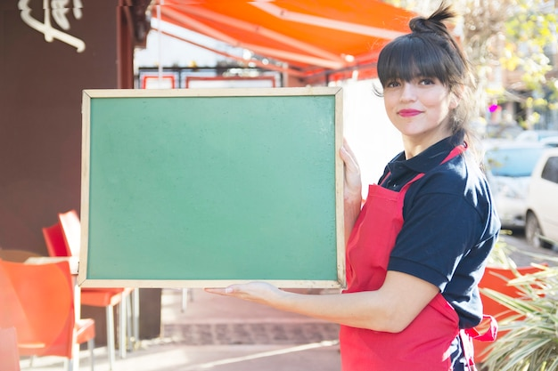 Confident female waitress holding blank green menu board at outdoors Free Photo