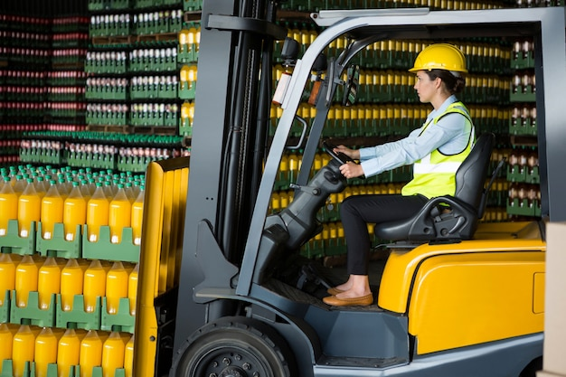 Confident female worker driving forklift in warehouse Free Photo