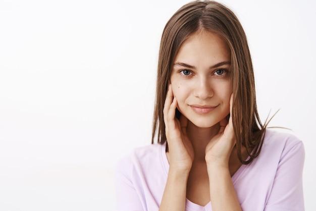 Fiducioso femminile attraente bruna femminile con i capelli lisci e la pelle pulita che tocca il viso delicatamente e sorridente audace flirtare sul muro bianco Foto Gratuite