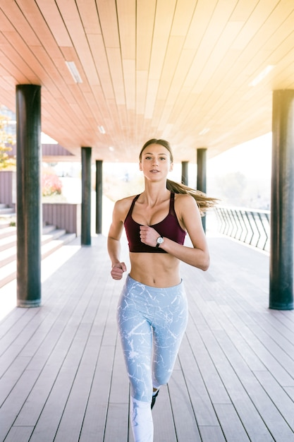Confident fitness young woman running in the morning Free Photo
