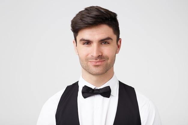 黒の蝶ネクタイで自信を持っていちゃつくハンサムなスマートな服を着た黒髪の男 無料写真