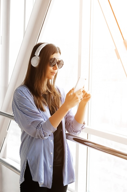 Confident girl or freelancer in headphones listening to music, looking at the phone while in the room, airport, office. mobile phone in the hands of stylish fashionable young women with glasses. Premium Photo