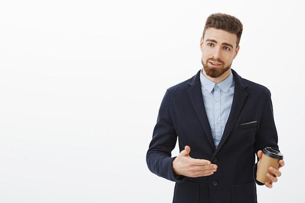 ひげと口ひげのエレガントなスーツジェスチャーで自信を持って見栄えの良いヨーロッパのビジネスマン 無料写真
