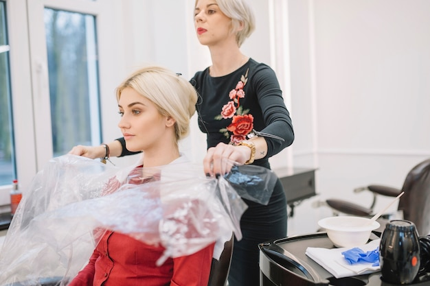 Confident hairstylist working with customer Free Photo