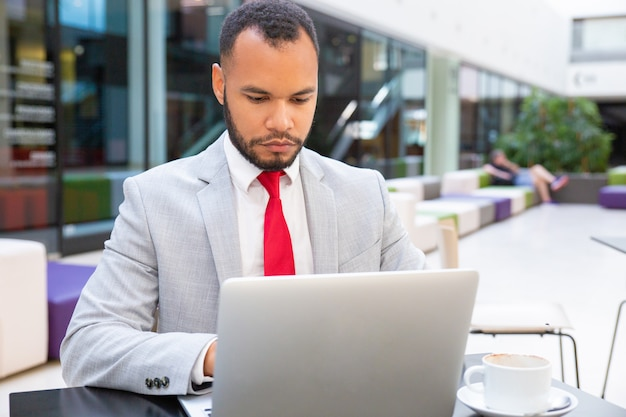 Confident handsome business leader using laptop Free Photo