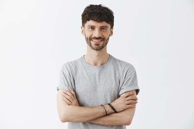 Уверенный красивый парень позирует у белой стены Бесплатные Фотографии