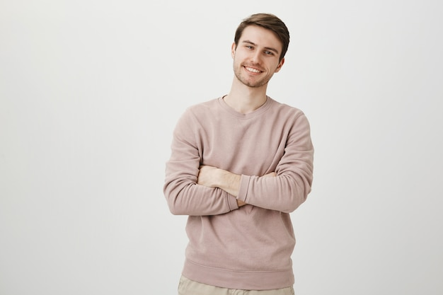 Confident handsome man smiling pleased, cross arms chest Free Photo