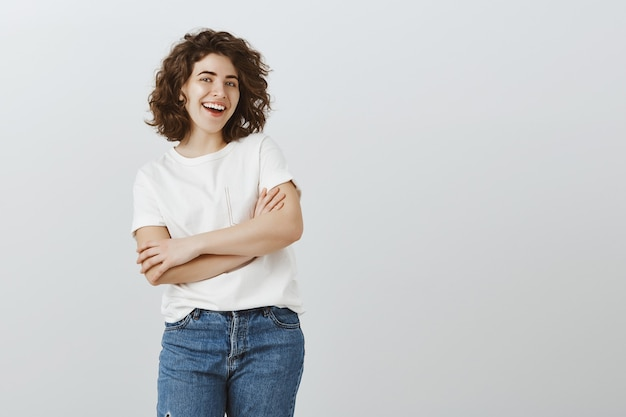 Confident happy female university student smiling with hands crossed Free Photo