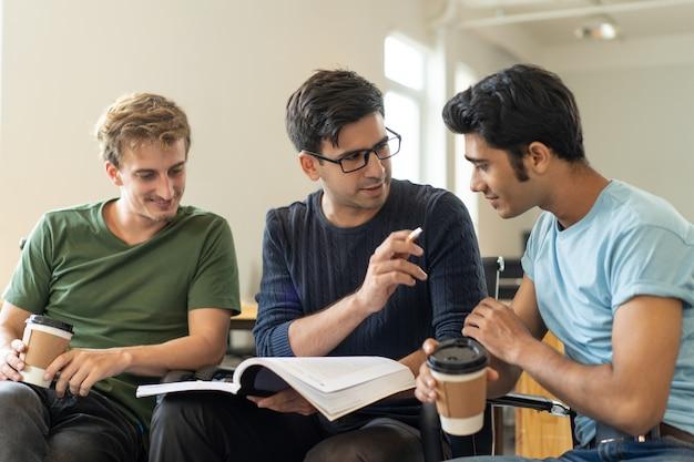 Confident hispanic guy explaining task to indian student Free Photo