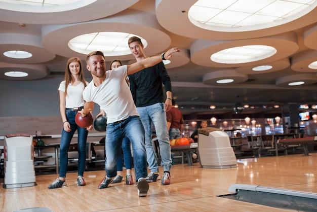 Уверен в своей силе. молодые веселые друзья веселятся в боулинг-клубе на выходных Бесплатные Фотографии