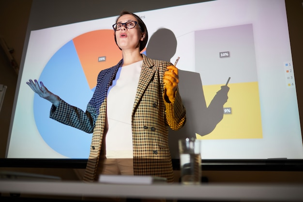 Confident lady explaining data on projection screen Premium Photo
