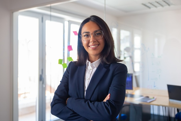 Confident latin business leader portrait. young businesswoman in suit and glasses posing with arms folded, looking at camera and smiling. female leadership concept Free Photo