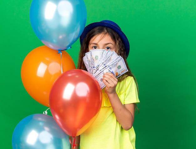 コピースペースと緑の壁に隔離されたヘリウム気球とお金を保持している青いパーティーハットを持つ自信を持って小さな白人の女の子 無料写真